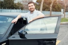 Man holding a car key next to his vehicle Stock Photography