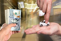 One man holding dollar banknotes, another man holding small car Stock Images