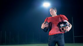 American football player holds his sports gear in hands, close up. stock video