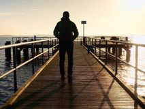The one man in hood looking on the sea from wooden hotel pier at morning. Stock Image