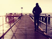 The one man in hood looking on the sea from wooden hotel pier at morning. Stock Photography