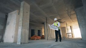 Person looking at a blueprint on a construction site, close up. stock footage