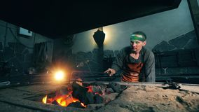 One man moves coal in fire with metal poker. Blacksmith forging iron in workshop. One man moves coal in fire with metal poker. 4K stock video