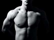 One man with muscular torso in the dark. Muscular male torso on black background Royalty Free Stock Photography
