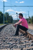 One man in pink t-shirt sitting on train tracks Royalty Free Stock Image
