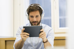 One man playing a video game on digital tablet interior Royalty Free Stock Photography