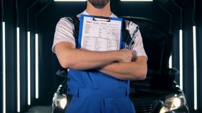 Repairman fixing a car. Car service concept. Repairman standing with a clipboard, close up. stock footage