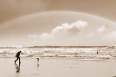 One man a rainbow and his dog Stock Photos
