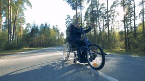 One man rides a special bicycle for disabled people. Paralyzed person rides on a road with the help of a special equipment stock footage