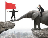 One man riding elephant another balancing nose toward red flag Stock Photo