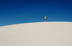 One Man's Journey. Solitary man walking along the top of a white sand dune, a metaphor for the journey of life Stock Image