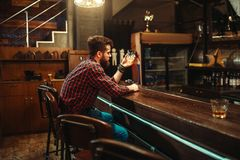 Man sitting at the bar counter and drink alcohol. One man sitting at the bar counter and drink alcohol beverage. Male person in pub stock image