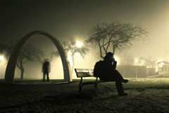 One man is sitting on the bench in foggy and mysterious park. Stock Image