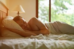 One man sleep in bed. In morning sunlight Royalty Free Stock Image
