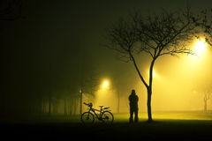 One man is standing and holding the bicycle in foggy and mysterious park. Stock Image