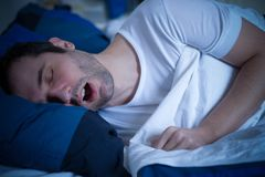 One man suffering of sleep apnea and snoring. Portrait of man sleeping and snoring loudly lying in the bed Stock Photos