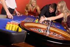 One man and two girls in casino Royalty Free Stock Image