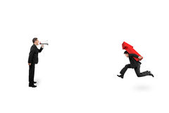 One man using speaker direct another carrying arrow up running Stock Photo