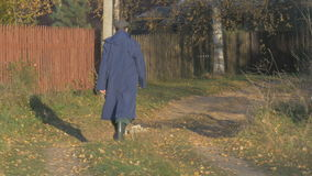 One man, walking along the road in the village at autumn day. Shallow focus. stock footage