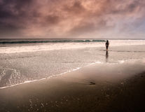 One man walking lonely. One man walking along the water's edge on a fantasy beach Royalty Free Stock Image
