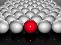 One of many. Single bright red ball in amongst many white balls Royalty Free Stock Image