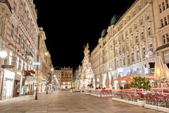 Pestsaule between illuminated buildings during night at Graben street in Vienna, Austria. One of many beautiful old buildings in the city of Vienna Stock Photo