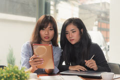 One-on-one meeting.Two young business women sitting at table in cafe. Girl shows colleague information on laptop screen. Girl using smartphone blogging stock photos
