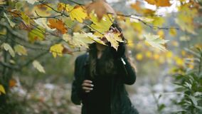 One middle eastern 25 years old woman walking in the nature and the fall season from defocus to focus area and smiling to the came stock video