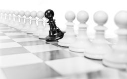 Only one in million. Single black pawn among many white ones Royalty Free Stock Photos