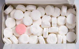 One mint standing out. One pink mint standing out amongst white mints Royalty Free Stock Photography