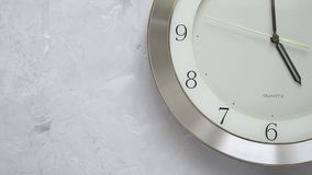 One minute before five on the wall clock with continuously moving time. Close up stock footage