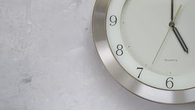 One minute after five on the wall clock with continuously moving time. Close up stock video footage
