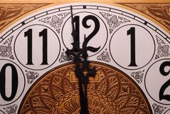 One Minute to Midnight. Close-up of the face of an old clock showing the time of one minute before twelve Royalty Free Stock Photo