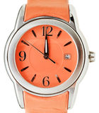 One minute to twelve o'clock on orange wristwatch Royalty Free Stock Images