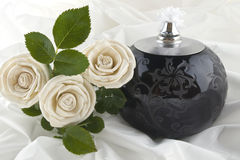For the one we miss. Roses and a oil lamp on satin Royalty Free Stock Photo