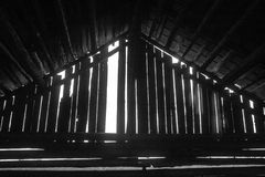 One Missing. A plank is missing of the wall of an old barn house. Looks a little like a temple royalty free stock photo