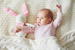 One month old baby girl with pink bunny stock image