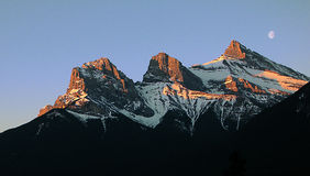 One moon and Three Sisters. Sunrise over the Three Sisters, Landmark in Canmore Stock Photos