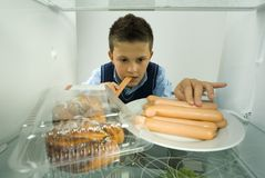 Only one more. Young boy eating greedily weiners from fridge. Front view Royalty Free Stock Images