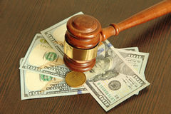 One more.Auction hammer and dollars on wooden table. Royalty Free Stock Photos