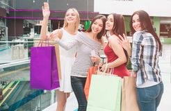 One more picture of fabulous and marvelous girls standing in mall with bags and posing. They are looking up, smiling and. Waving. Girl in red dress hold phone stock images