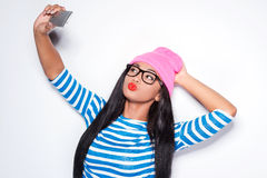 One more selfie!. Happy young African woman in funky clothes making selfie with her smart phone while posing against white background Royalty Free Stock Images