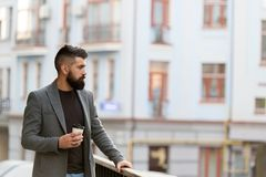 One more sip of coffee. Enjoying coffee on the go. Businessman well groomed appearance enjoy coffee break out of. Business center. Relax and recharge. Man stock photo