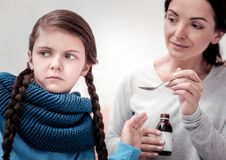 Close up of upset child with cough syrup. One more spoon. Close up of little upset child looking away while her mother holding cough syrup and giving it to her stock images