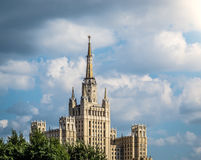 One of Moscow`s famous highrises. Blue cloudy sky in background, tree in foreground. Summer in Russia stock photography