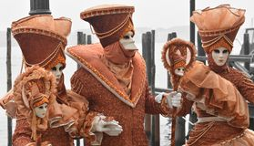 The disembarkation at Piazza San Marco of four masks disguised in orange costume. One of the most beautiful carnivals in the world in the city, Venice, the most Stock Photography