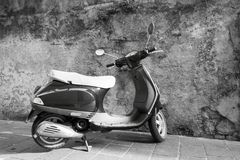 One motor scooter closeup against a stone wall Stock Photo