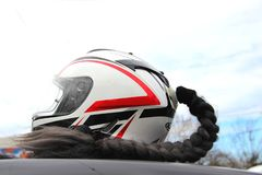 One Motorcycle helmet is white with red and black stripes with black braided hair on the roof of a black car. stock images