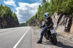 One motortraveler with own motorbike resting on roadside on mountain asphalt road Royalty Free Stock Image