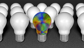 One multicolored iridescent light bulb among many white ones on grey textured background Royalty Free Stock Photo